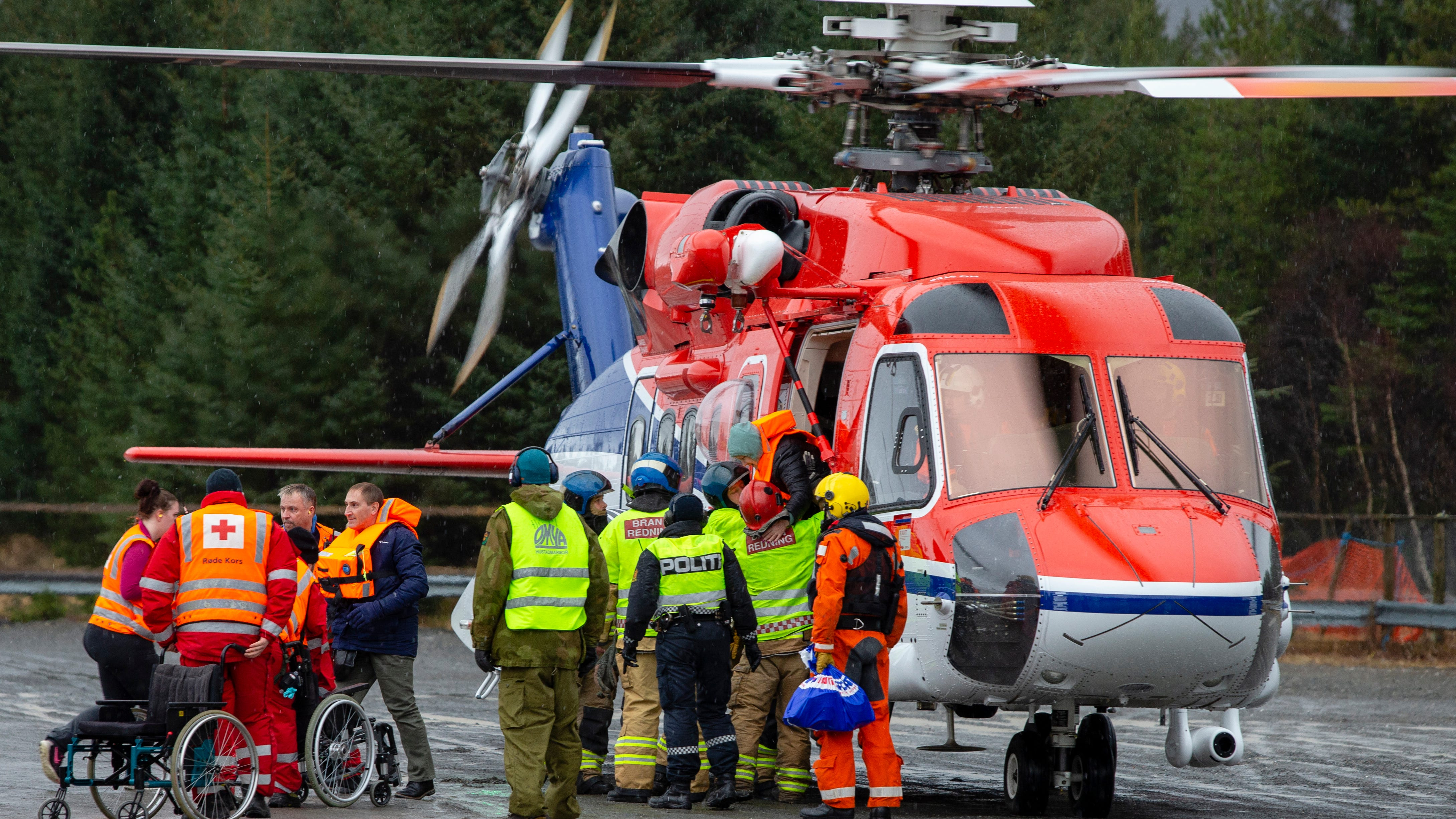 Passengers are helped from a rescue helicopter in Fraena, Norway, Sunday March 24, 2019, after being rescued from the Viking Sky cruise ship.