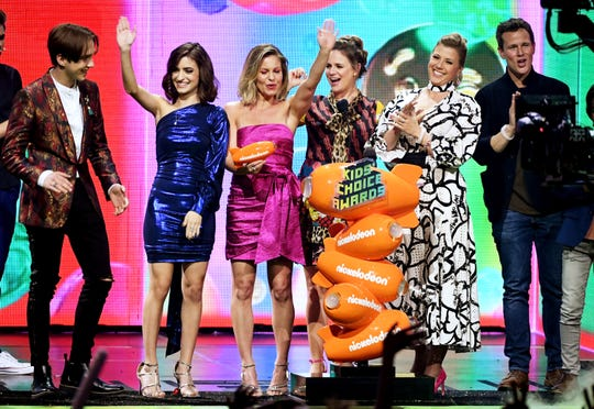 """The cast of """"Fuller House"""" – Michael Campion, Soni Bringas, Candace Cameron-Bure, Andrea Barber, Jodie Sweetin and Scott Weinger – accept the favorite-funny TV show award at Nickelodeon's 2019 Kids' Choice Awards."""