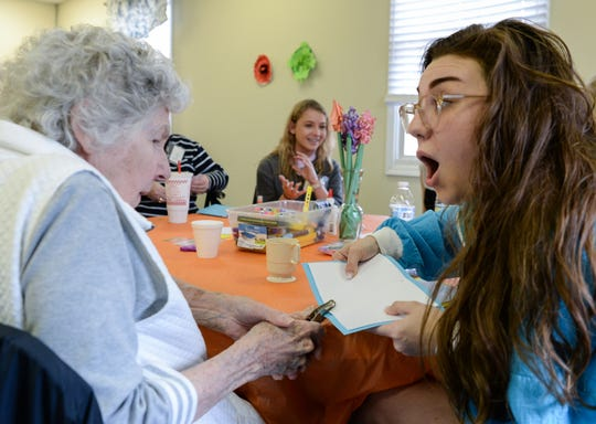 Betty Gray, left, punches a hole in paper with Clemson University Health Science student Hunter Vaughn, right, during the I.E.A Brain Health Club at the Central-Clemson Recreation Center in Central Monday. The two were making a homemade journal notebook.