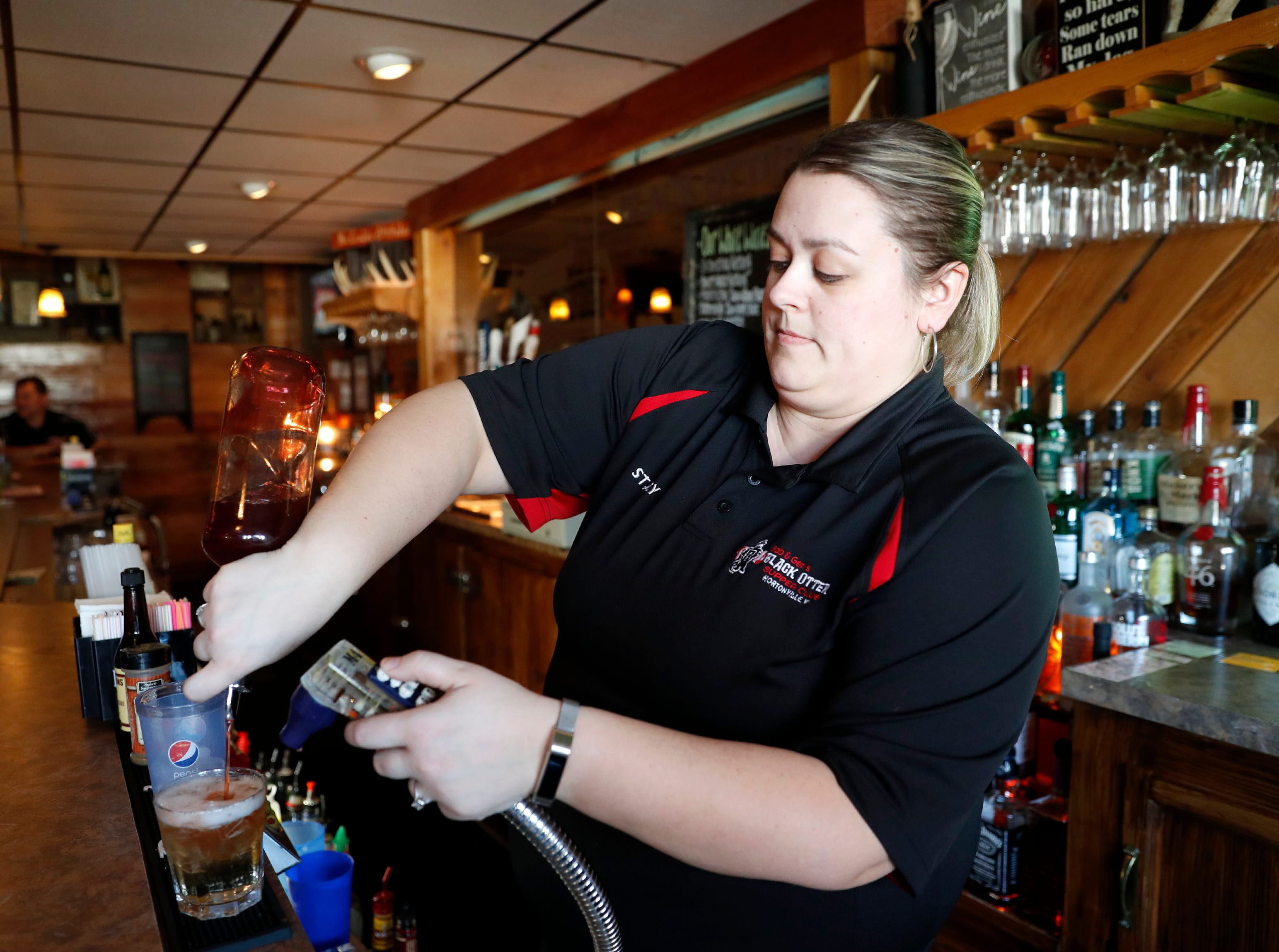 Stacy Jens, a bartender at Black Otter Supper Club, pours a drink for a customer Thursday, March 21, 2019, in Hortonville, Wis. 