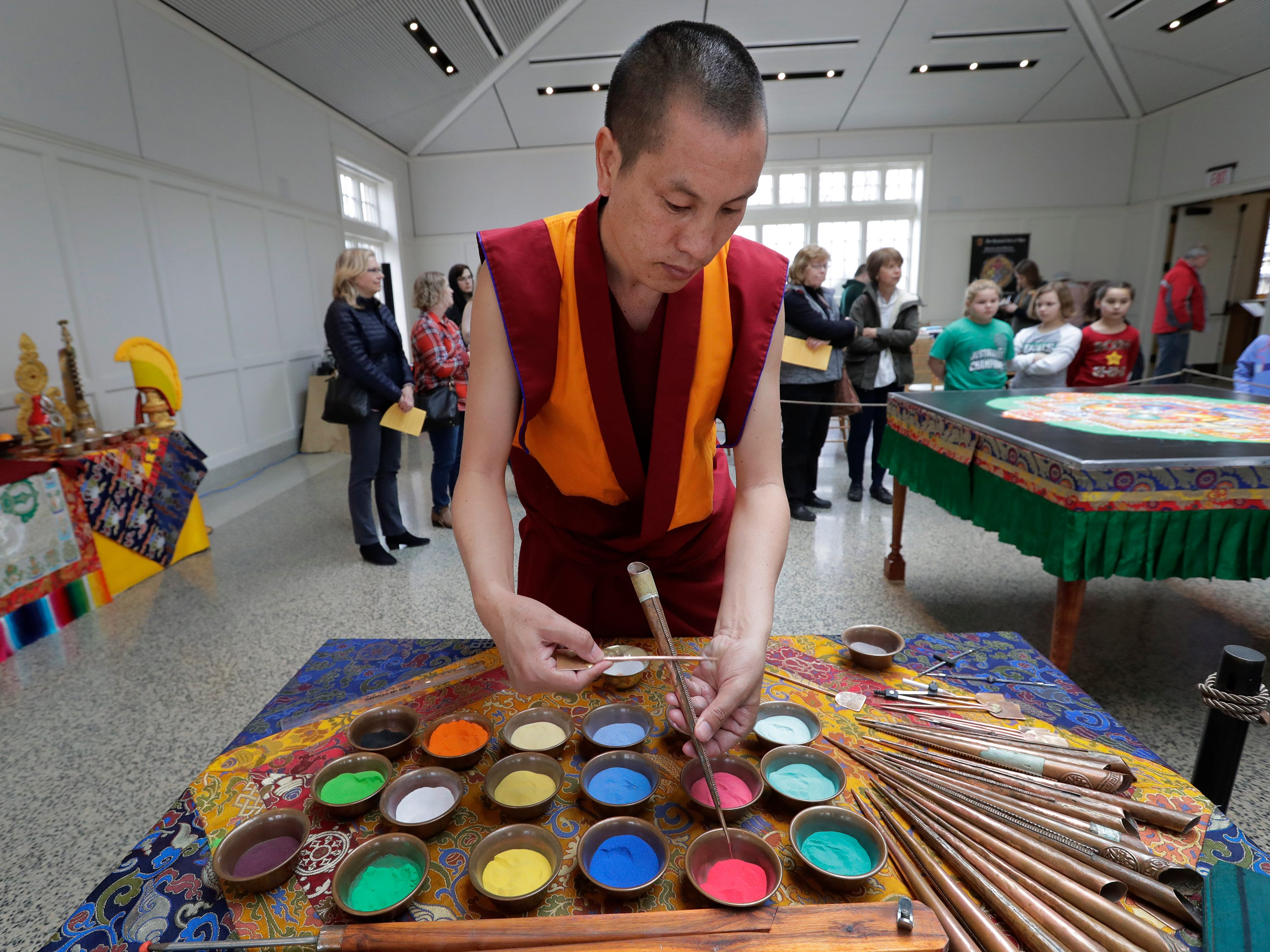 Lobsang Dorjee, a Buddhist monk from Drepung Loseling Monastery in south India, empties sand from a Chak-pur tool while creating a Mandala Thursday Thursday, March 21, 2019, at The Paine Art Center and Gardens in Oshkosh, Wis. Dan Powers/USA TODAY NETWORK-Wisconsin