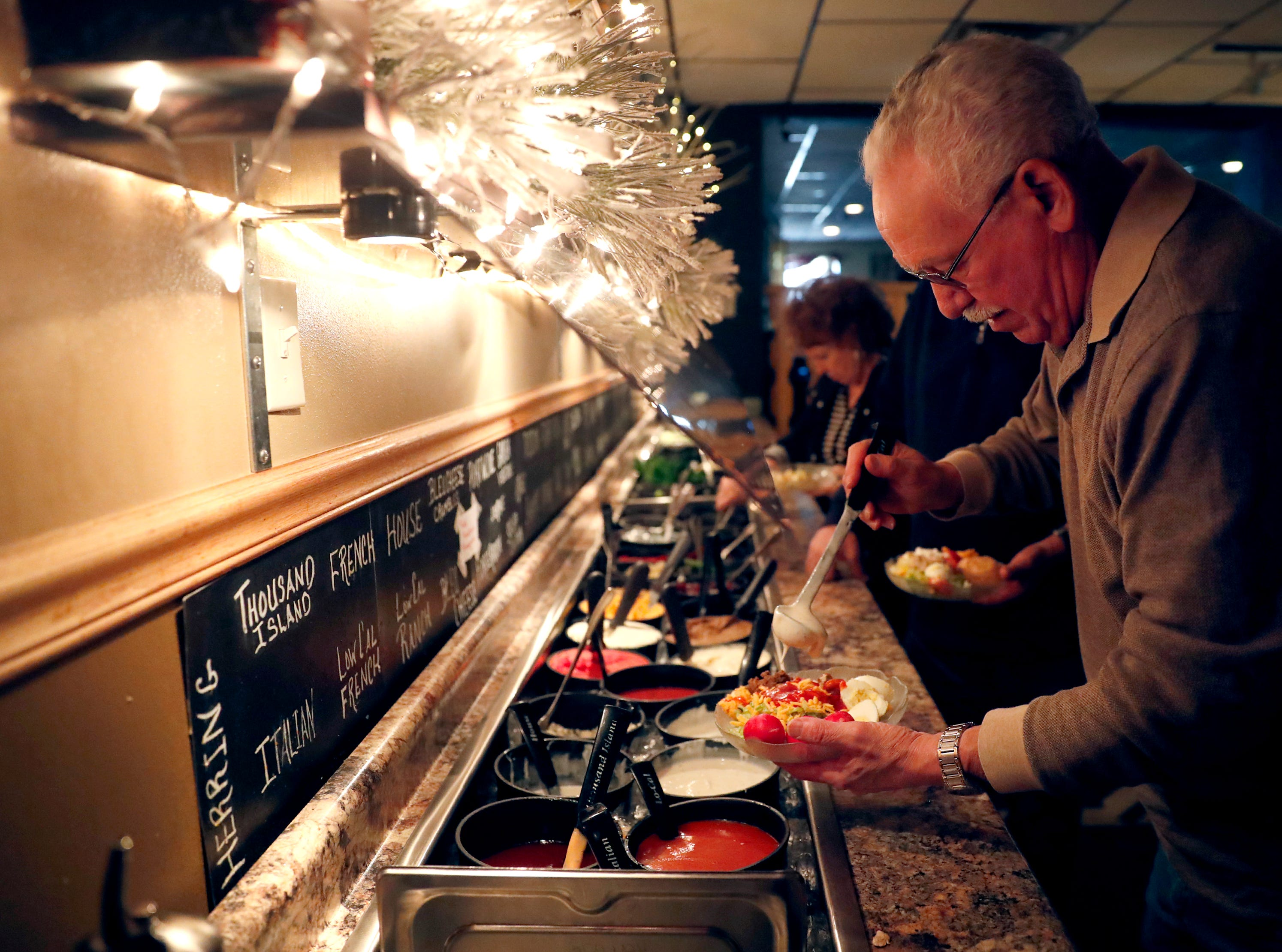 Roger Parkhurst, of Wild Rose, makes his way through the Black Otter Supper Club salad bar Thursday, March 21, 2019, in Hortonville, Wis. 