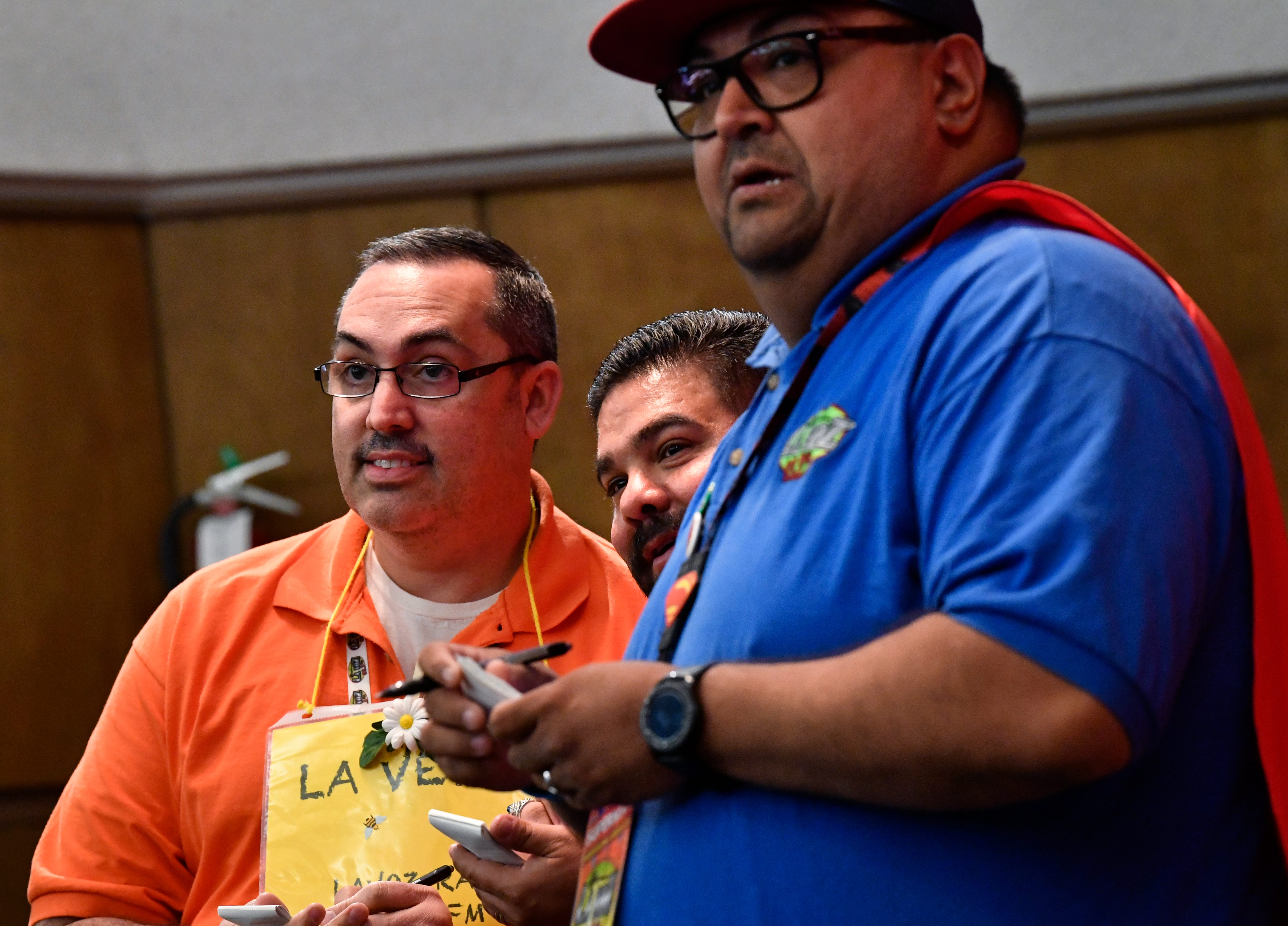 From left, Pete Garcia, Carlos Serna,and Superman Vizcaino from LaVoz radio listen to emcee George Levesque repeat a medical term for them to spell.