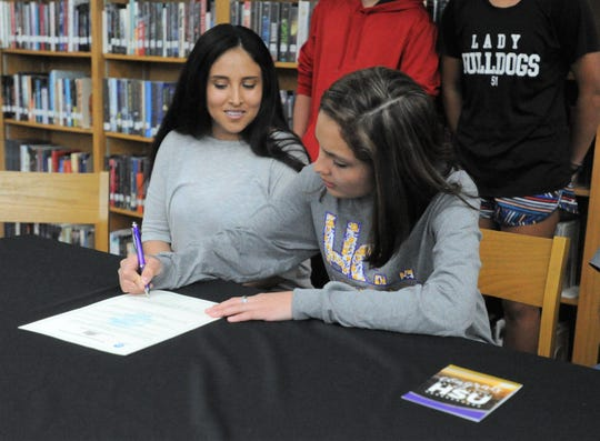 Clyde senior Alex Phariss signs her letter to run cross country at Hardin-Simmons at a celebration Monday, March 25, 2019, at Clyde High School.