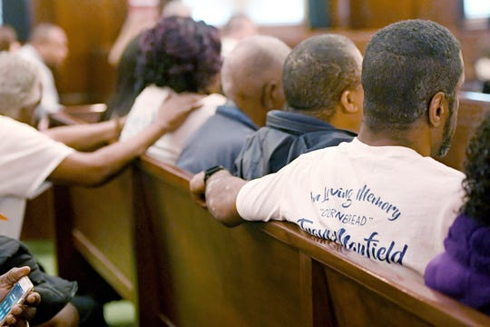 Family members of Travis Mayfield wear shirts in his memory as they comfort one another as Frederick Nathaniel Simpson and Travoscia Herbell Brown plead guilty to voluntary manslaughter in his November 2016 shooting death at the Buncombe County Courthouse on March 25, 2019.