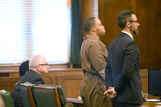 Travoscia Herbell Brown, standing with his lawyer, pleads guilty to voluntary manslaughter in the November 2016 shooting death of Travis Mayfield at the Buncombe County Courthouse on March 25, 2019.
