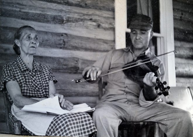 Doug Wallin is seen here on the porch of his log cabin home at the head of Crane Branch.