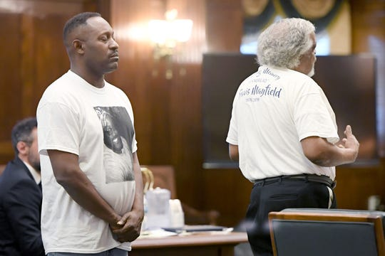 Travis Mayfield's cousin Duane Hall wears a shirt with his photo on it as he listens to Mayfield's father, Aquila Mayfield Sr., give a victim statement during the plea hearing for Frederick Nathaniel Simpson and Travoscia Herbell Brown who pleaded guilty to voluntary manslaughter in the November 2016 shooting death of Mayfield at the Buncombe Count Courthouse on March 25, 2019.