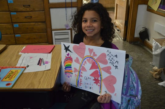 """Sophia Diaz, 7, is one of the children in Voces Elementary Literacy Program participating in the Michigan 4-H China Project. Her artwork features a rainbow surrounded by pink hearts and an ice cream cone. In the corner, Sophia wrote """"Pik me"""" because she's hoping her art is one of the ones that gets sent to China."""