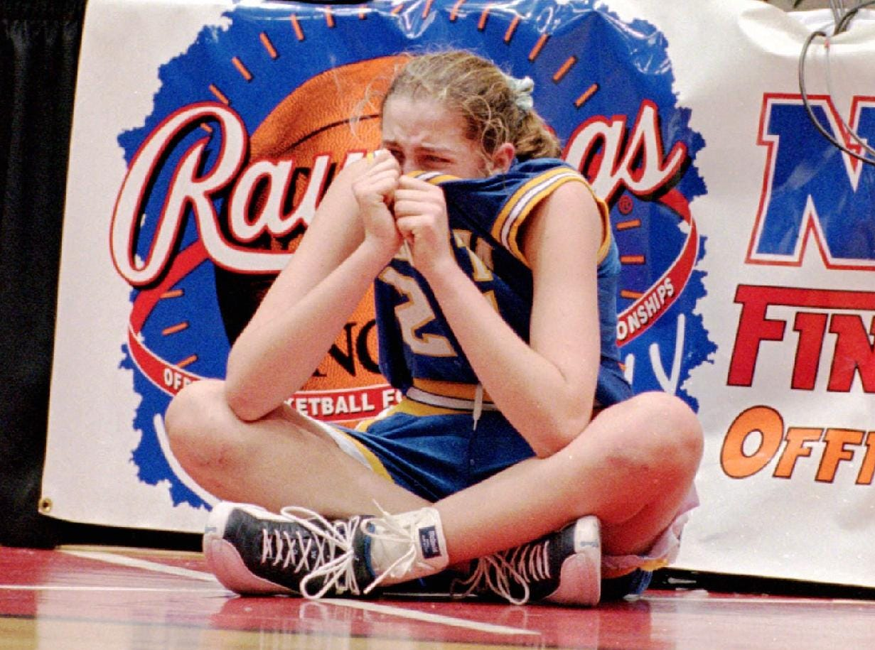 Krissy Zeh, foreground, a tenth-grader at Oneonta High School, hides her face in her jersey as she waits to sub in Oneonta's Federation Class B girls' championship game against Holy Angels Adademy of Buffalo, Sat, Mar 22, 1997. Holy Names won, 53-45.