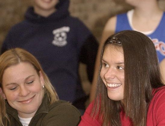 2004: Kyle Dougherty, right, writes her signature to confirm her intent to play basketball at Villanova next year as Owego Free Academy varsity coach Samantha Riegal looks on Monday at Owego Free Academy High School.