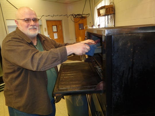 Michael Haynes takes some food out of the oven inside the kitchen of Boulevard United Methodist Church. He has served as the chef and head volunteer at a soup kitchen held at the church for the past 16 years.