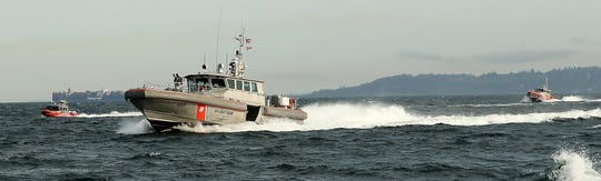 Coast Guard boats head for a memorial ceremony off Blake Island on Monday.