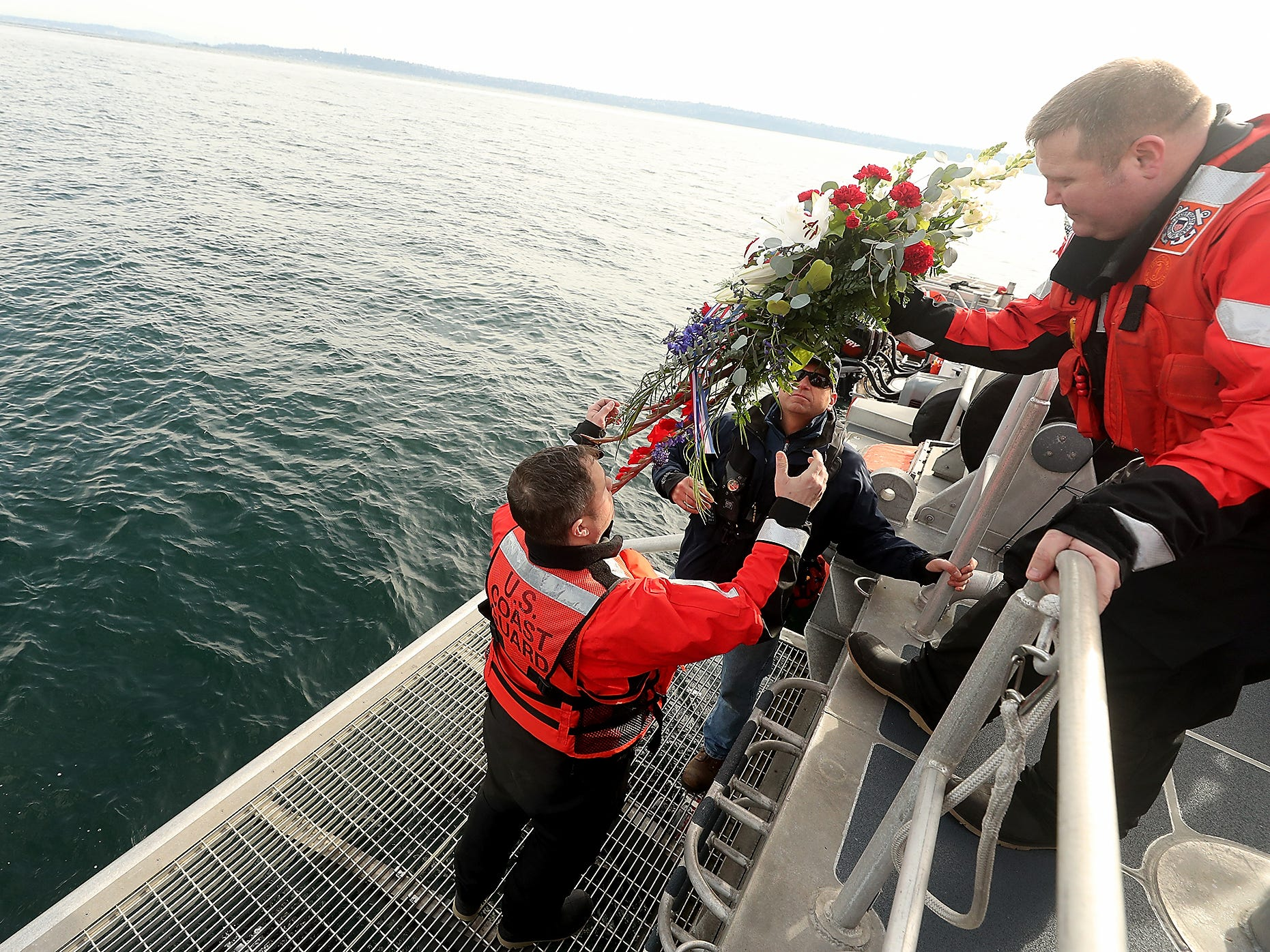 USCG Chief Boatswain Mate Aaron Balazs (right) hands the wreathe down to Chief Boatswain Mate Brandon Alani (left) and Chris Mogavero as they prepare to place the wreath in the water in memory of Petty Officer Ronald Gill on Monday, March 25, 2019. Gill was killed in 2007 when he was ejected from his patrol boat while conducting maritime homeland security operations in Puget Sound.
