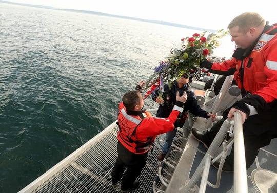 Chief Boatswain Mate Aaron Balazs, right, hands a wreath down to Chief Boatswain Mate Brandon Alani, left, and Chris Mogavero as they prepare to place it in the water in memory of Petty Officer Ronald Gill on Monday. Gill was killed in 2007 when he was ejected from his Coast Guard patrol boat.