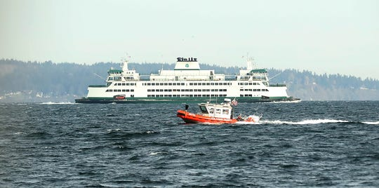 A Coast Guard patrol boat passes the Washington State Ferry Chimacum before the start of a wreath-laying ceremony for Petty Officer Ronald Gill on Monday.