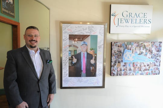 Nathaniel Ruland stands next to a framed photo of his father David, who founded Grace Jewelers in 1999. David retired in February and Nathaniel took over the family business.