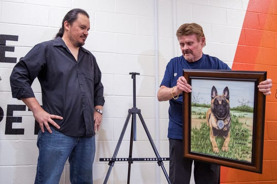 Artist Jody Bustillos (left) and Denny Bales unveil a commissioned artwork of the Corpus Christi Police Department's newest officer, Damon, a Belgian Malinois, during an event at the Gulf Coast Humane Society on Monday, March 25, 2019.