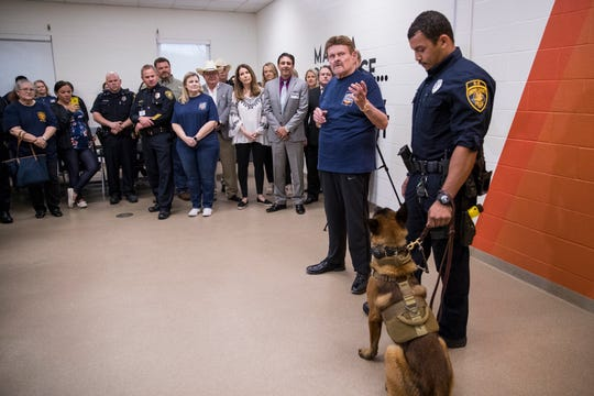 Denny Bales (left) and Corpus Christi Police Department Officer and K-9 handler Devin Haywood participate in the pinning of the police department's newest officer, Damon, a Belgian Malinois, during an event at the Gulf Coast Humane Society on Monday, March 25, 2019.