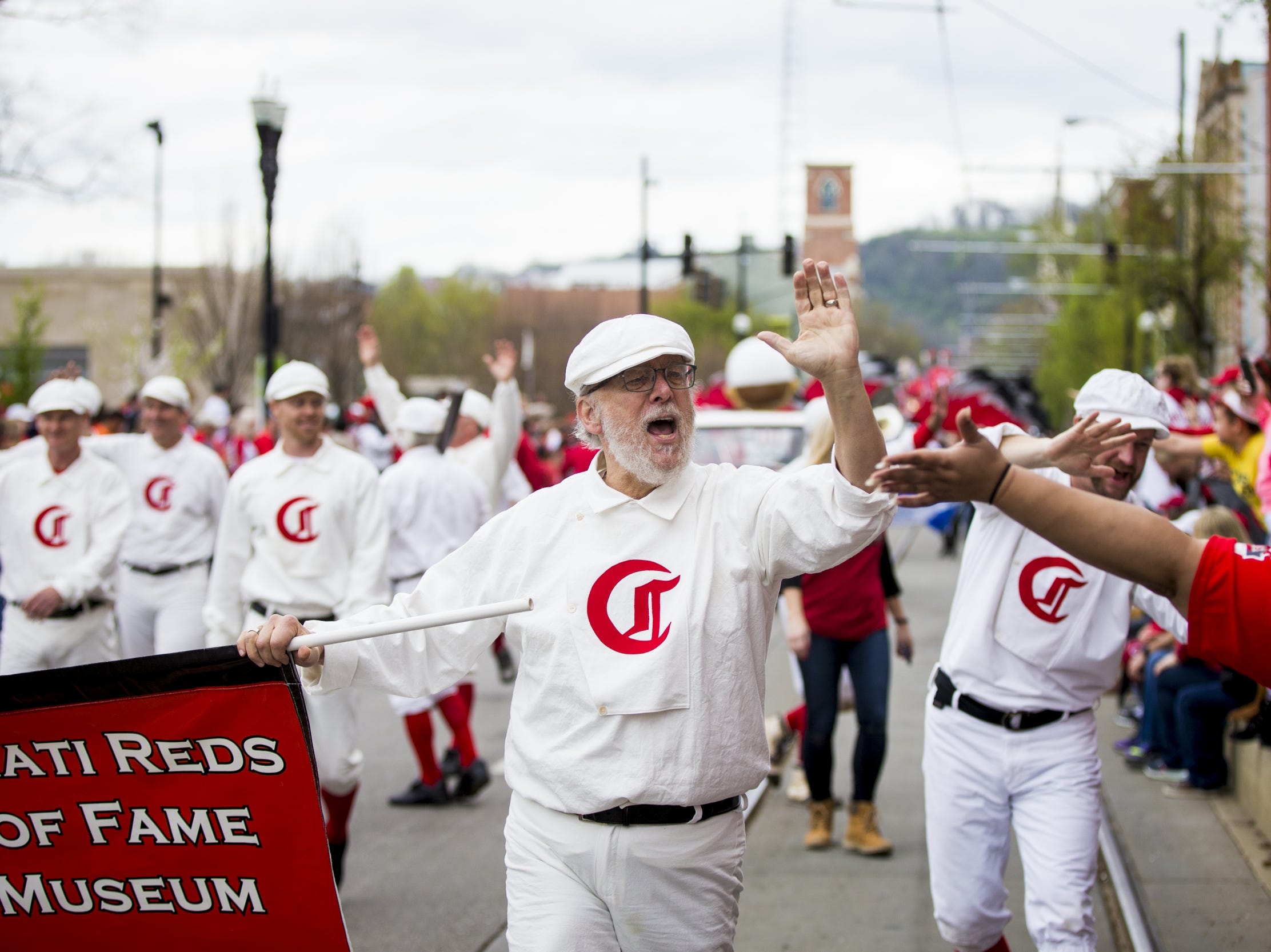 April 3, 2017: Representatives of the Cincinnati Reds Hall of Fame and Museum greet people along the Findlay Market Opening Day parade route.