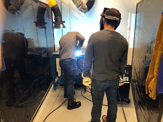 Students in an American Welding Society MIG welding class at Raritan Valley Community College in Branchburg practice using a welding gun during class.