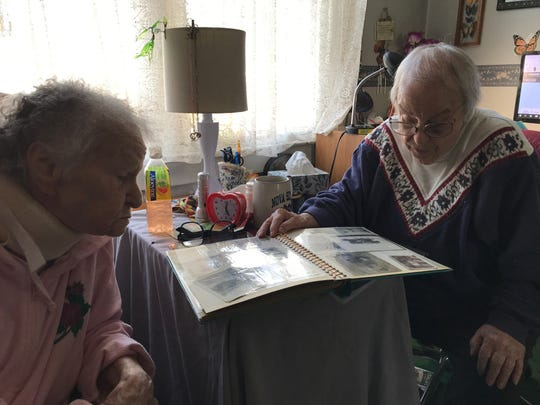 Olga Anderson of Edison and her sister Mary Yaverski of Dunellen look over a photo album with pictures of their brother U.S. Army Sgt. Frank J. Suliman of Edison who was killed in action during the Korean War.