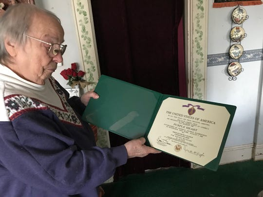 Mary Yaverski holds her brother Sgt. Frank J. Suliman's certificate of Purple Heart.