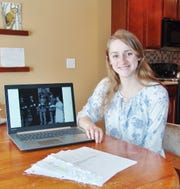 """Annalissa Hankinson posing with materials she used to produce her documentary """"Dennison's Railroad WWII Canteen."""" The Walhonding student is interested in studying history in college and earned an honorable mention for her documentary in a national competition sponsored by C-SPAN."""