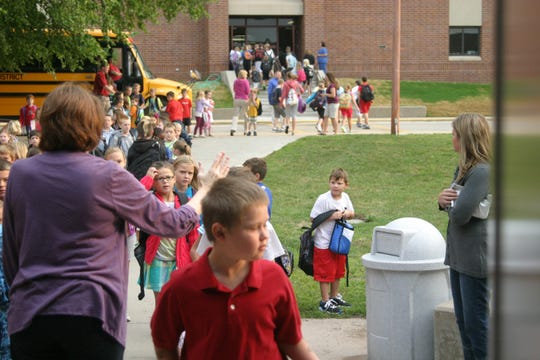 An Anderson Elementary counselor welcomes students with high fives on the first day of school in 2012.
