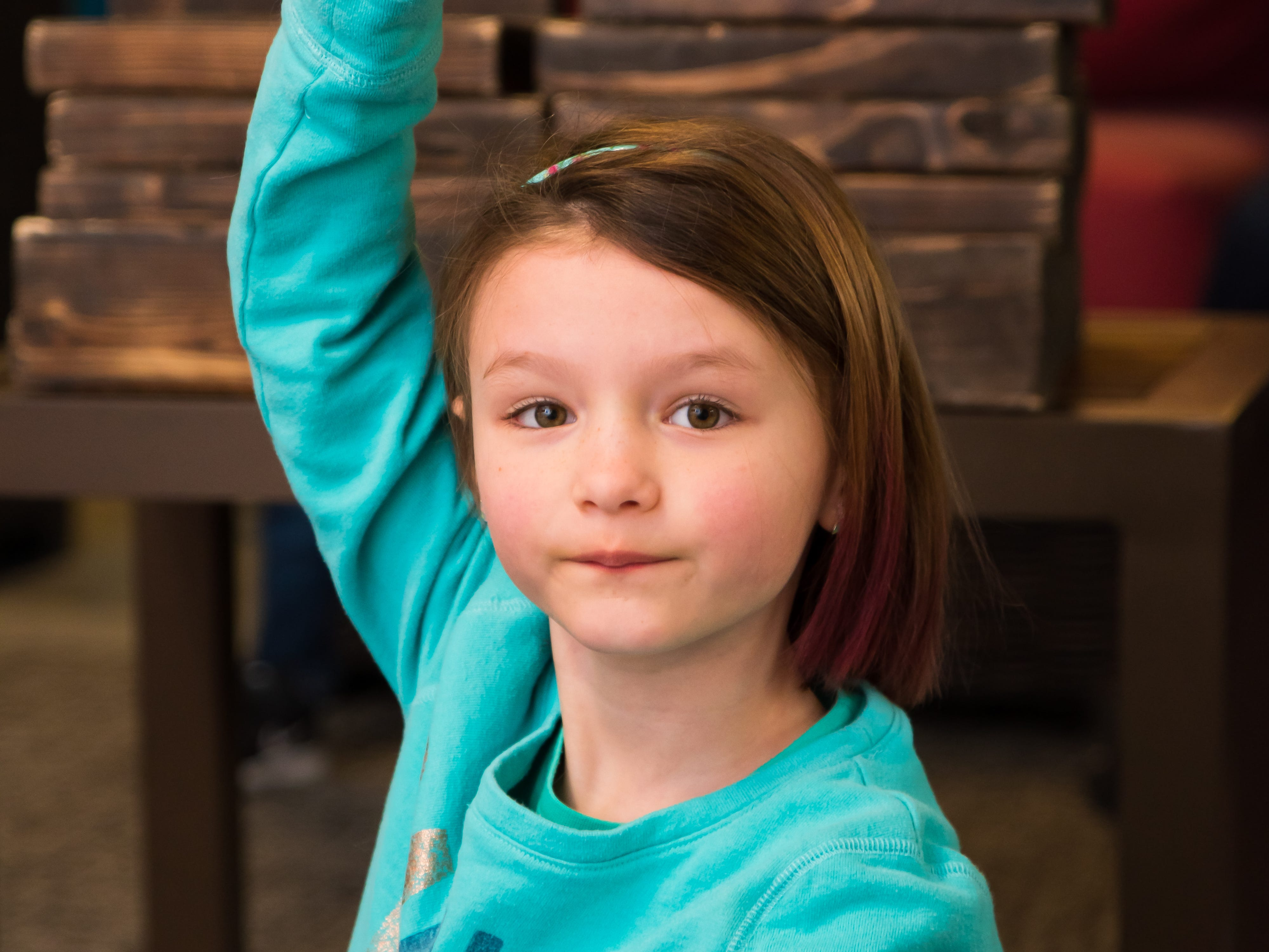 Emarie Mitchell, 7, of Altoona raises her hand to answer a question Wednesday, March 20, 2019, during a Science Center program at the Outlets of Des Moines in Altoona.