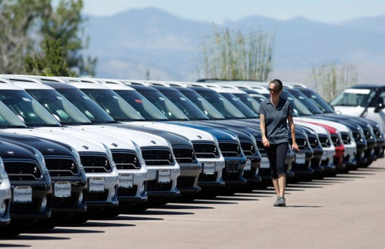 FILE --In this Aug. 30, 2018 photo, a lot technician passes by 2018 and 2019 Countryman models at a Mini dealership in Highlands Ranch, Colo.