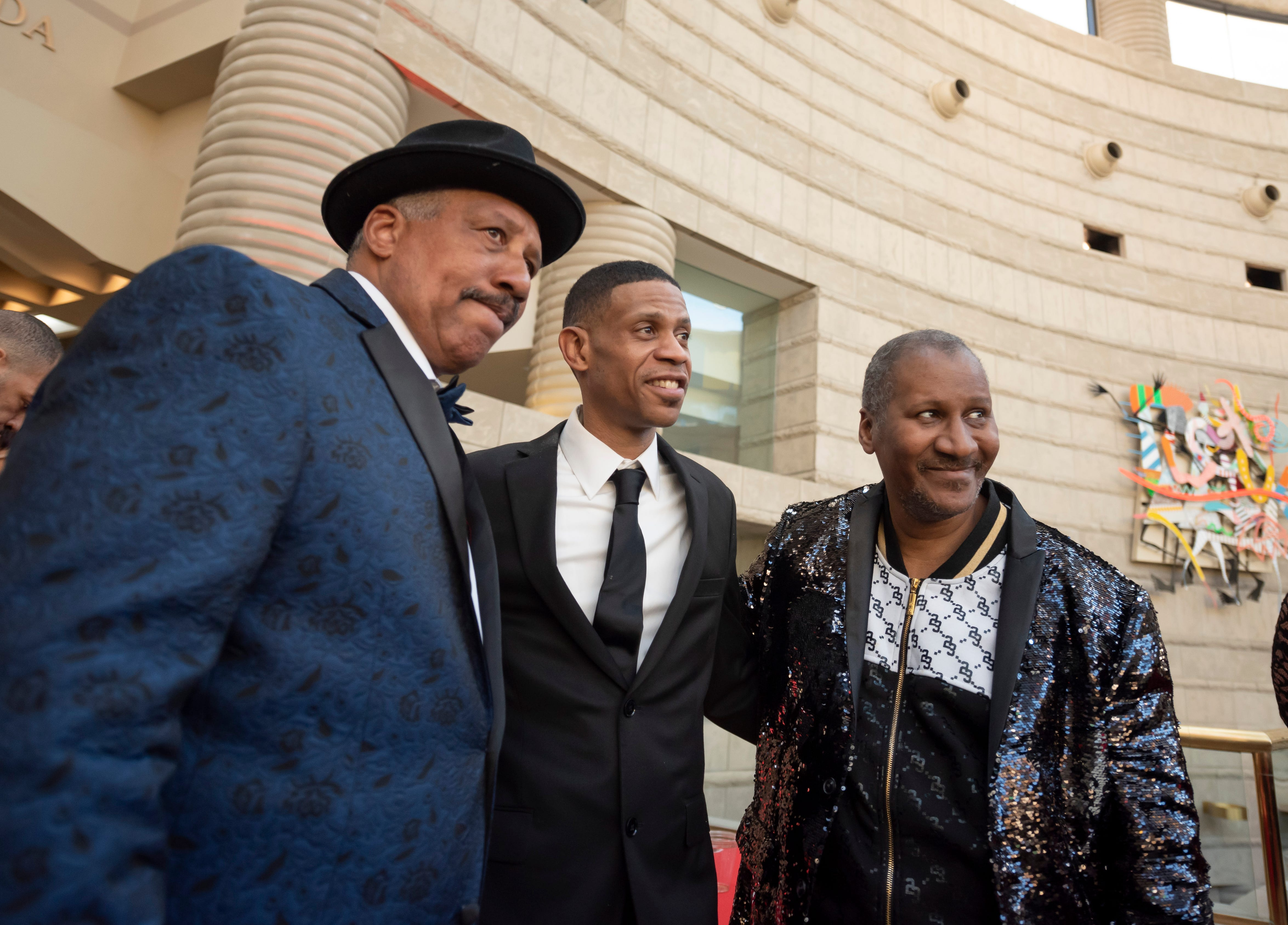 """Three of Aretha Franklin's son, Edward, Kecalf, and Clarence, pose for photos during a reception prior to the premiere of the Aretha Franklin concert film """"Amazing Grace"""" at the Charles H. Wright Museum of African American History in Detroit, Monday evening."""