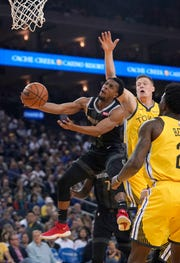 Detroit Pistons guard Ish Smith (14) drives to the basket against Golden State Warriors forward Jonas Jerebko, right rear, during the first half.