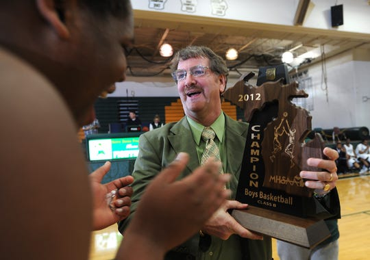 Kurt Keener hands a Class B regional championship trophy to his Country Day players in 2012.