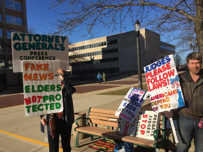 Victoria McCasey of Holly and Randy Asplund of Ann Arbor protest outside a Lansing press conference announcing a statewide elder abuse task force on Monday, March 25, 2019. The small group protesting Monday expressed hope that the task force launched by Attorney General Dana Nessel would investigate the legal system around guardianships, conservatorships and estates.