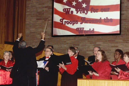 Paul Holland conducts the Common Time Choral Group during a prayer service in December of 2003 for overseas troops at Pennsylvania Avenue United Methodist Church in Pine City.