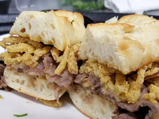 The Prime Dip with shaved prime rib, smoked Gouda cheese and onion straws on a toasted garlic baguette with au jus and horseradish.