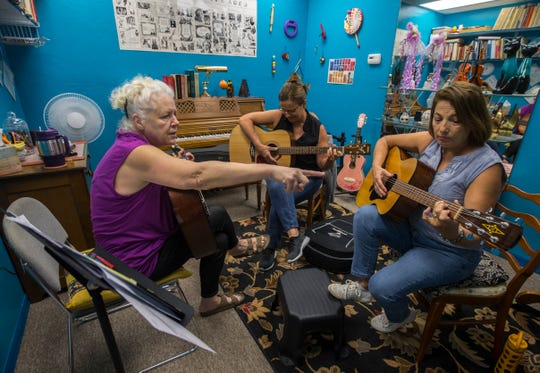 From left, Barbara McCubbin, owner of McCubbin's Music Conservatory in Cape Coral, conducts a guitar lesson for sisters Laurie Lewis and Christine Antle.
