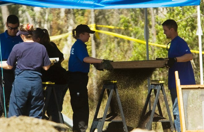Investigators with the Florida Department of Law Enforcement and the Fort Myers Police Department sift through dirt that was found at the remains of eight bodies found off of Arcadia Street in Fort Myers on Friday.