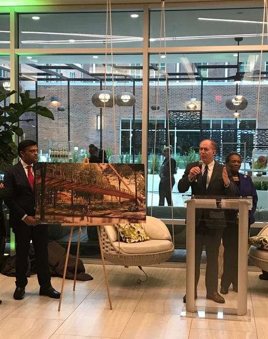 Mayor Knox White speaks as Auro Hotels president and CEO DJ Rama stands next to a rendering of the Auro Bridge at Unity Park during a grand opening at the Residence Inn/Springhill Suites dual-brand hotel in downtown Greeenville.