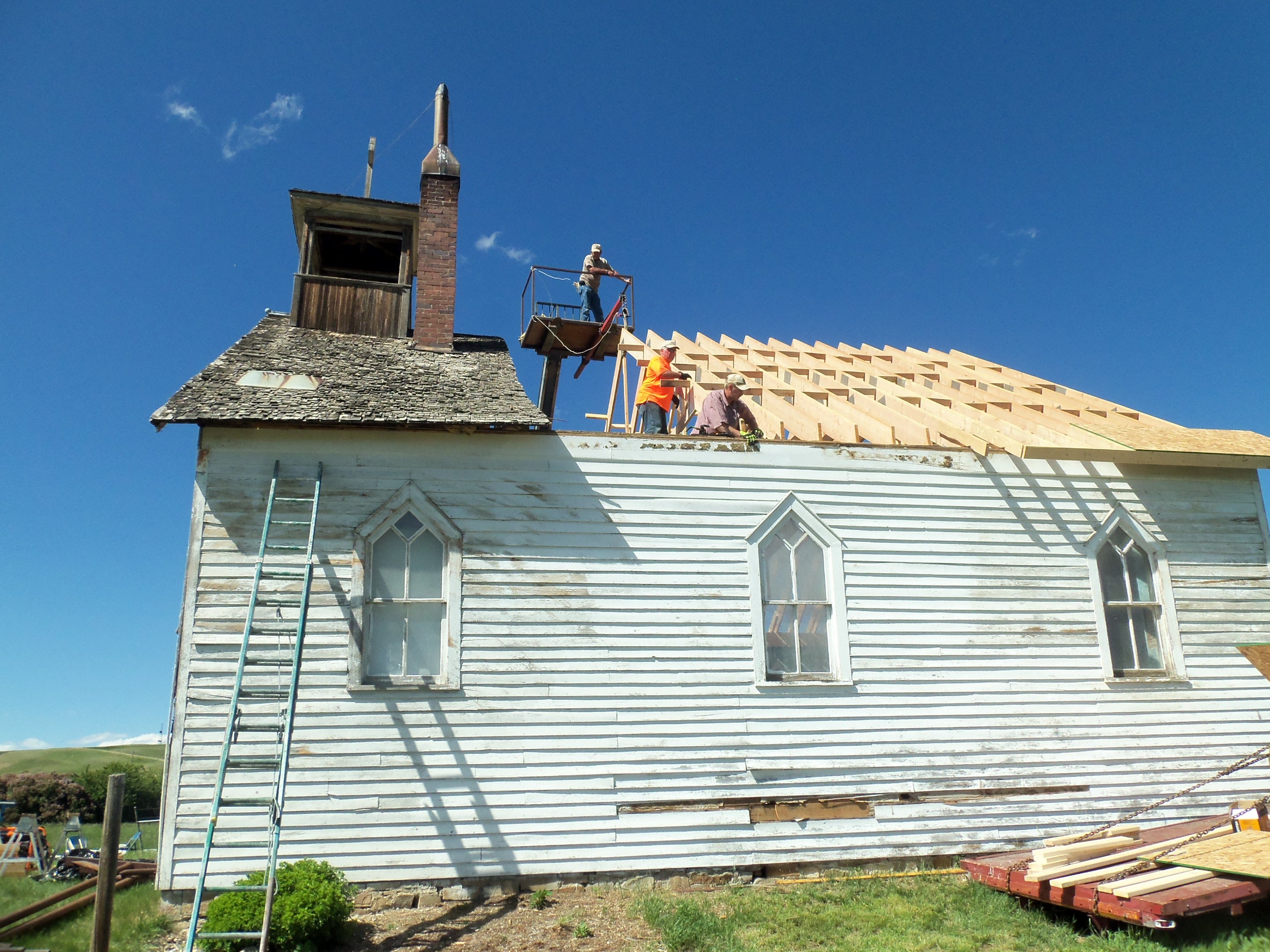 Photo courtesy of Tony Fowler Volunteers work to replace the roof of Sacred Heart Church east of Valier during the summer of 2013.
