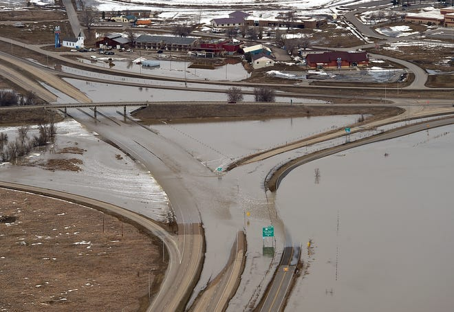 The I-90 and Highway 212 intersection floods as the Little Bighorn River covers roads, homes and fields near Crow Agency, Mont. on Sunday, March 24, 2019.
