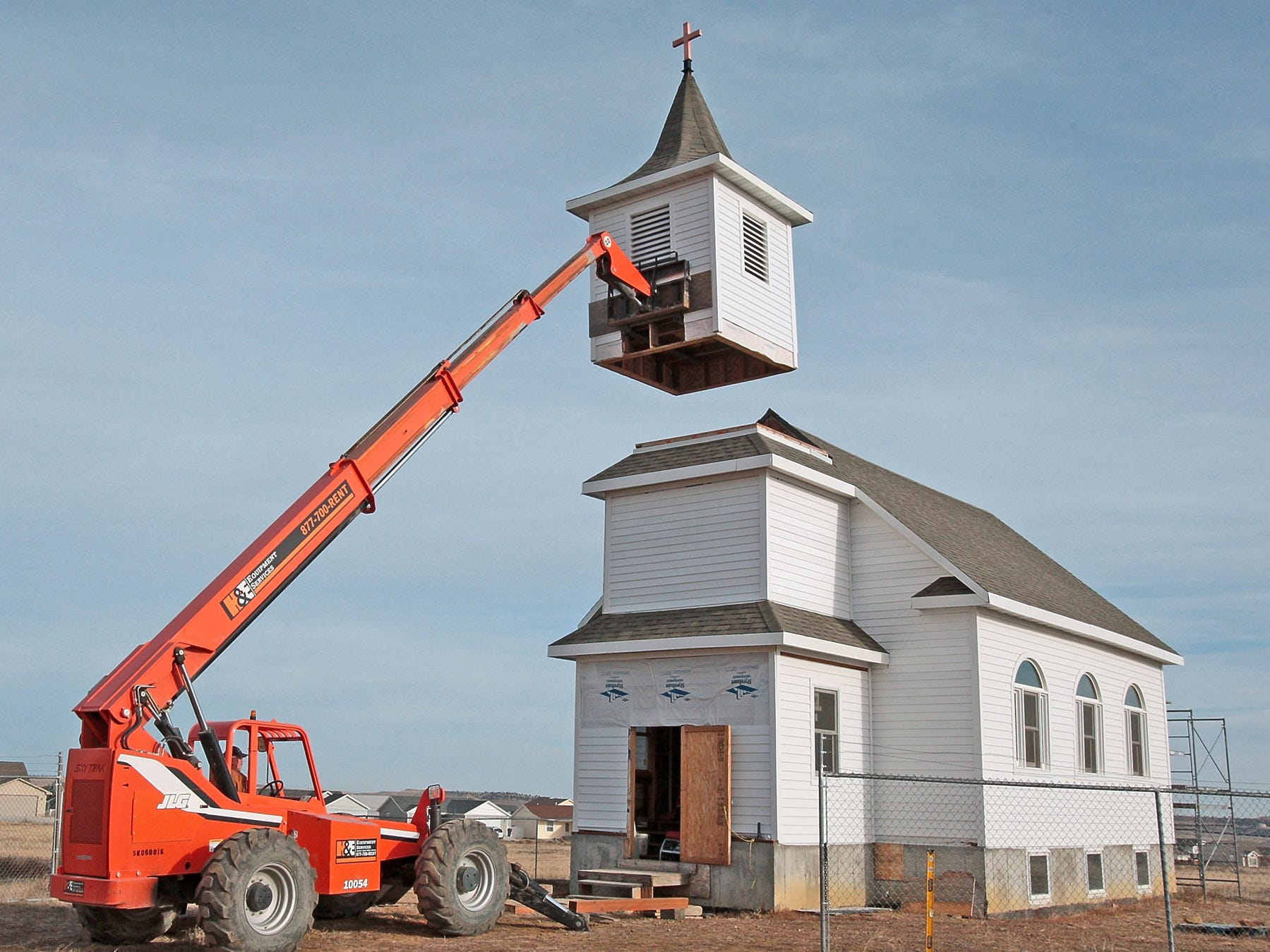 In this Nov. 20, 2009 photo, Jack Beals uses a forklift to lift the steeple, of the Little White Church on the hill, back into place in Billings, Mont. The church located near Skyview was moved to Billings from Box Elder in 2006 and will be part of a St. John's Lutheran Ministries development in Billings Heights. The steeple was removed for the move and needed extensive repairs.
