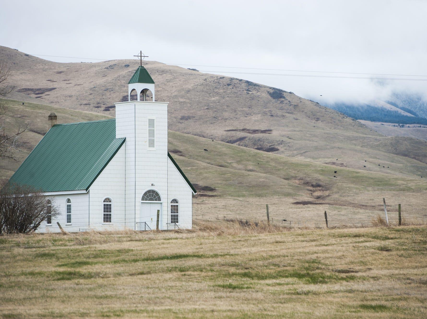 The Presbyterian church in Whitlash is set against a fog-enshrouded East Butte.