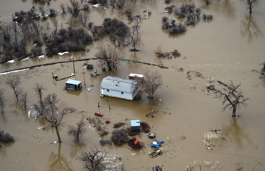 The Little Bighorn River covers roads, homes and fields near Crow Agency on Sunday, March 24, 2019. A spokesman for the Crow Tribe, Justin Stewart, said the tribe has been working to help people in remote locations or without drinking water because water from recently repaired water mains haven't been deemed safe to drink yet.