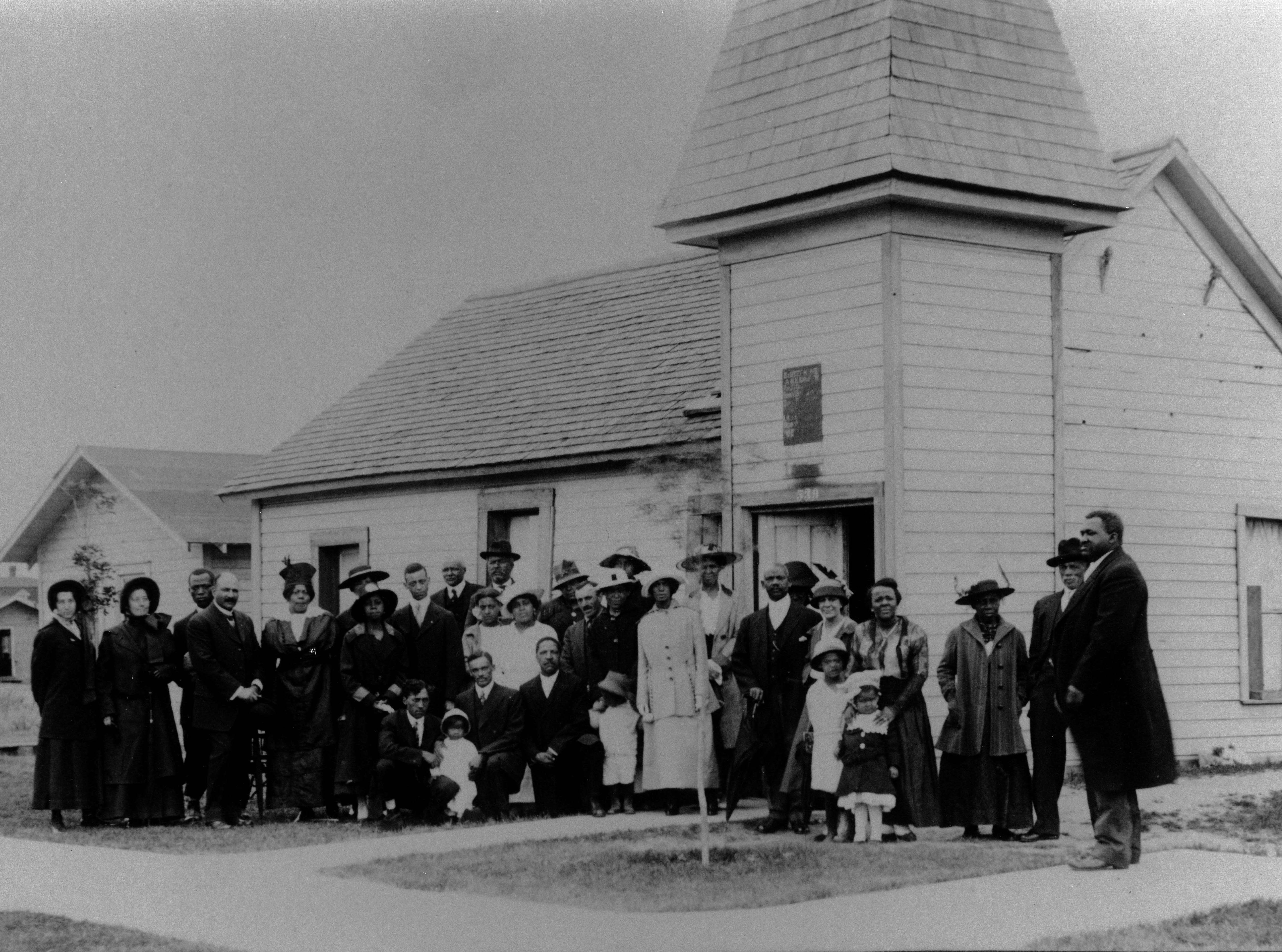 The congregation of the African Methodist Episcopal Church gathers in front of its original building in 1916 before it was torn down to make way for a new church, which still stands today at 916 5th ave. s.