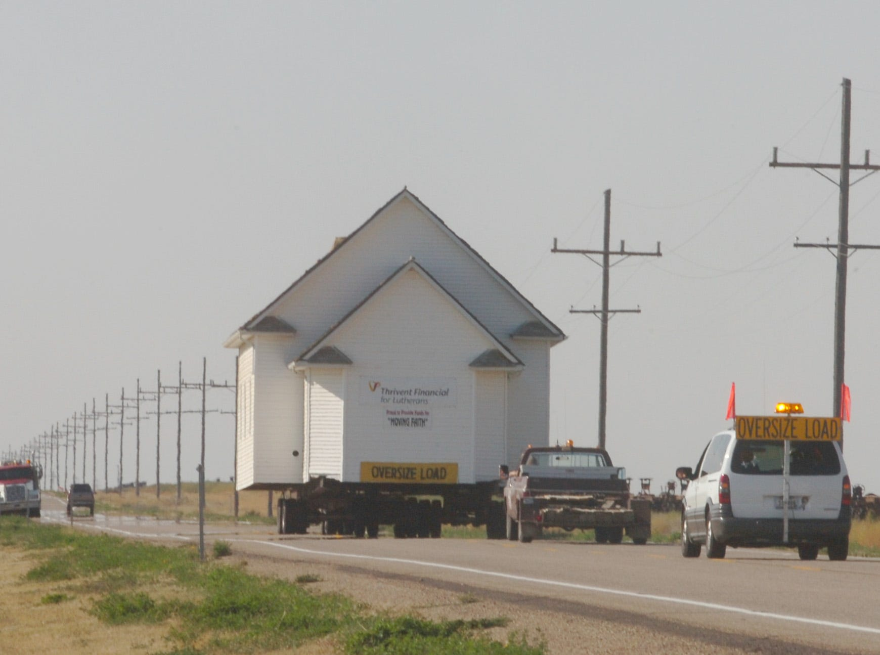 The Faith Lutheran Church building heads south from Box Elder on U. S. Highway 87 in 2006.  It is being moved to Billings by Ostermiller Housemoving.