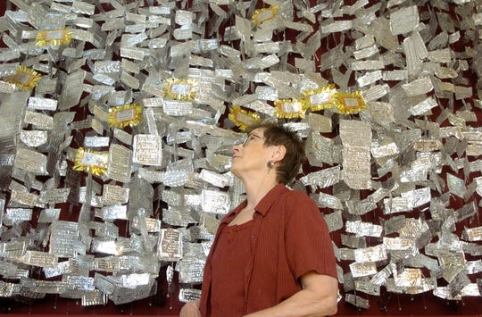 """Jean Price looks at her art installation, """"Two-thousand and Counting,"""" a tribute to the more than 2,000 soldiers who have died since the beginning of the war in Iraq. In 2006, Price embossed the name rank and age of each fallen soldier on a piece of aluminum tooling foil and strung them on a piece of mono filament.  The copper name plates represent Montana soldiers who died since the war began in March 2003 and was installed at the Paris Gibson Square Museum of Art."""