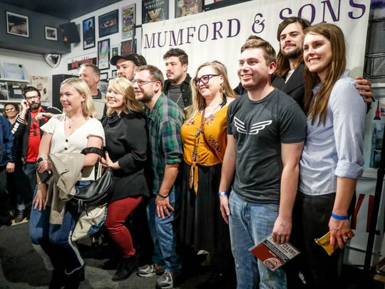 Fans pose with members of Mumford & Sons following Monday's in-store performance at Indy CD & Vinyl.