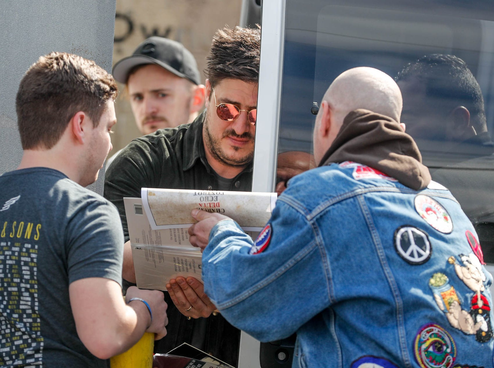 Mumford & Sons fans Michael Stebing, left, and Lindsay Banach get an autograph from band member Marcus Mumford, after the band's special in-store appearance at Indy CD & Vinyl on Monday, March 25, 2019.